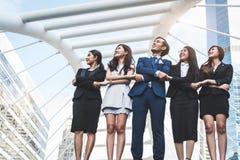 St?ende av den lyckade gruppen av aff?rsfolk som upp till ser himmel som framtid Lyckliga affärsmän och affärskvinnalag in arkivbild