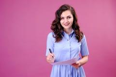 St?ende av den lyckliga kvinnan med ett papper och en penna som g?r listan och t?nker ?ver rosa bakgrund royaltyfri fotografi