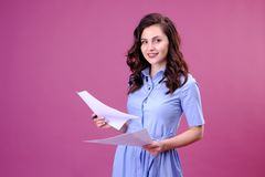 St?ende av den lyckliga kvinnan med ett papper och en penna som g?r listan och t?nker ?ver rosa bakgrund arkivfoton