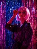 St?ende av den lyckliga le flickan i peruk och den stilfulla glamor?sa kl?nningen med paljetter royaltyfri fotografi