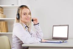 St?ende av den lyckliga le kvinnliga operat?ren f?r telefon f?r kundservice p? arbetsplatsen royaltyfri bild