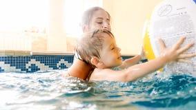 St?ende av den lyckliga le litet barnpojken som l?r simning med modern i p?l Familj som har gyckel och kopplar av i simning royaltyfri bild