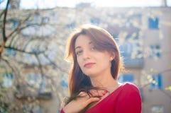 St?ende av den stilfulla le lyckliga brunettkvinnan som utomhus g?r under solig v?rdag, medan solen skiner royaltyfria foton