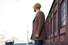 St?ende av den stilfulla stiliga unga mannen i exponeringsglas med borstet som utomhus st?r B?rande omslag och skjorta f?r man royaltyfri foto