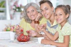 St?ende av den stora lyckliga familjen som ?ter nya jordgubbar arkivbild