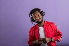 St?ende av den unga afrikanska mannen som lyssnar till musik med h?rlurar arkivbilder