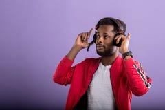St?ende av den unga afrikanska mannen som lyssnar till musik med h?rlurar arkivfoton