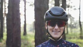 St?ende av den unga attraktiva cykla kvinnan som b?r den svarta hj?lmen och exponeringsglas och le Cykla begrepp l?ngsam r?relse arkivfilmer