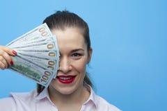 St?ende av den unga glade aff?rskvinnan som rymmer amerikanska dollarr?kningar royaltyfria foton