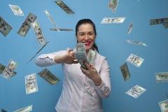 St?ende av den unga glade aff?rskvinnan som tycker om pengarkassafanen royaltyfri bild