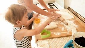 St?ende av den unga h?rliga kvinnan som undervisar hennes pojke f?r litet barn som g?r kakor och hemma bakar pajer p? k?k royaltyfri fotografi