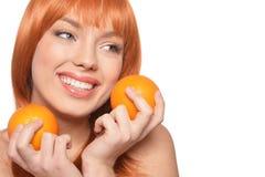 St?ende av den unga kvinnan som poserar med apelsiner p? vit bakgrund arkivbilder