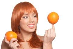 St?ende av den unga kvinnan som poserar med apelsiner p? vit bakgrund arkivbild