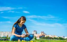 St?ende av den unga ton?ringbrunettflickan med l?ngt h?r flickan med en smartphone och hörlurar som sitter på gräset i, parkerar  arkivfoton