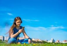 St?ende av den unga ton?ringbrunettflickan med l?ngt h?r flickan med en smartphone och h?rlurar som sitter p? gr?set i, parkerar  arkivbilder