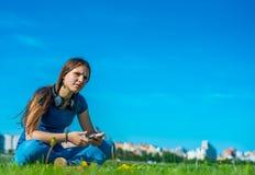 St?ende av den unga ton?ringbrunettflickan med l?ngt h?r flickan med en smartphone och h?rlurar som sitter p? gr?set i, parkerar  fotografering för bildbyråer