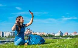 St?ende av den unga ton?ringbrunettflickan med l?ngt h?r flickan med en smartphone och h?rlurar som sitter p? gr?set i, parkerar  royaltyfria foton