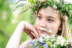 St?ende av en blond flicka med en krans av blommor i sommaren n?ra tr?det royaltyfri foto