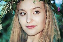 St?ende av en blond flicka med en krans av blommor i sommaren n?ra tr?det royaltyfri fotografi