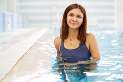 St?ende av en f?rdig ung kvinna i simbass?ngen r royaltyfria foton