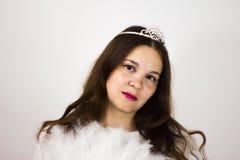 St?ende av en flicka i en krona och med en vit fan royaltyfria bilder