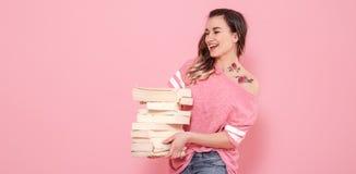 St?ende av en flicka med en bunt av b?cker p? en rosa bakgrund royaltyfri fotografi