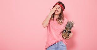 St?ende av en flicka med ett st?ngt ?ga p? en rosa bakgrund royaltyfria bilder