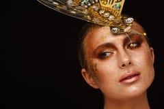 St?ende av en h?rlig kvinna med uttrycksfullt id?rikt smink i brons och med en garnering p? hennes huvud royaltyfria bilder