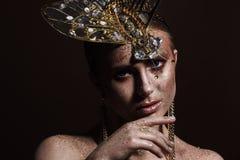 St?ende av en h?rlig kvinna med uttrycksfullt id?rikt smink i brons och med en garnering p? hennes huvud royaltyfri foto