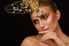 St?ende av en h?rlig kvinna med uttrycksfullt id?rikt smink i brons och med en garnering p? hennes huvud arkivbild