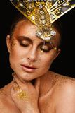 St?ende av en h?rlig kvinna med uttrycksfullt id?rikt smink i brons och med en garnering p? hennes huvud arkivfoton