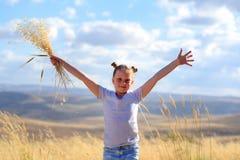 St?ende av en h?rlig liten flicka i mitt av ett vetef?lt royaltyfri bild