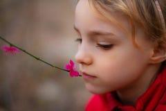 St?ende av en h?rlig liten flicka med blommor arkivfoto