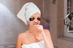 St?ende av en h?rlig ung kvinna efter dusch i lappar kvinnliga borstet?nder framme av hennes badrumspegel healty wellness royaltyfria foton