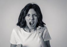 St?ende av en h?rlig ung kvinna med den ilskna framsidan som ser rasande M?nskliga uttryck och sinnesr?relser arkivfoto