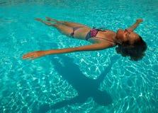 st?ende av en h?rlig vit kvinna som tycker om en avslappnande lugna tidsimning i det genomskinliga vattnet av en p?l i en solig d royaltyfria foton