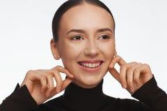St?ende av en kvinna med ett intressant utseende i en svart halvpolokrage och med samlat h?r arkivbild