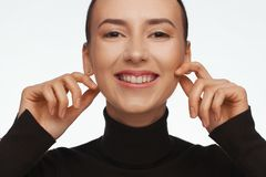 St?ende av en kvinna med ett intressant utseende i en svart halvpolokrage och med samlat h?r royaltyfri fotografi