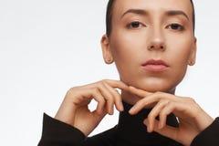 St?ende av en kvinna med ett intressant utseende i en svart halvpolokrage och med samlat h?r arkivfoton