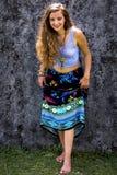 St?ende av en lycklig ung flicka och en kl?dd blom- maxi kjol med ?verkanten arkivfoto