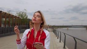 St?ende av en lyssnande musik f?r lycklig flicka p? h?rlurar fr?n en smartphone i gatan i en solig dag f?r sommar stock video