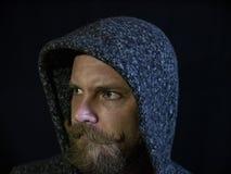 St?ende av en man med ett sk?gg och mustaschen i huven med en allvarlig framsida p? en svart bakgrund arkivfoto