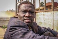 St?ende av en medel?lders svart man Arbetarlastbil i ett smutsigt omslag royaltyfri fotografi