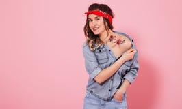 St?ende av en stilfull flicka i grov bomullstvillkl?der p? en rosa bakgrund arkivbilder