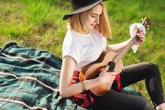 St?ende av en ung h?rlig kvinna i en svart hatt Flicka som sitter p? gr?set och spelar gitarren royaltyfri bild