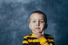St?ende av ett fundersamt gulligt litet barn med handen som trycker p? framsidan som ser kameran arkivbilder