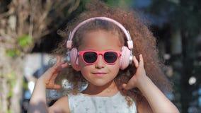 St?ende av ett gulligt barn, en underbar liten h?rlig flicka i en vit kl?nning med rosa exponeringsglas och rosa h?rlurar stock video