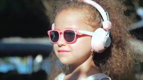 St?ende av ett gulligt barn, en underbar liten h?rlig flicka i en vit kl?nning med rosa exponeringsglas och rosa h?rlurar arkivfilmer