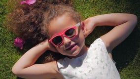 St?ende av ett gulligt barn, en underbar liten h?rlig flicka i en vit kl?nning och rosa exponeringsglas som ligger p? gr?set stock video
