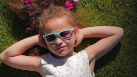 St?ende av ett gulligt barn, en underbar liten h?rlig flicka i en vit kl?nning och rosa exponeringsglas som ligger p? gr?set lager videofilmer